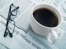 A cup of coffee, glasses and a newspaper Stock Photo
