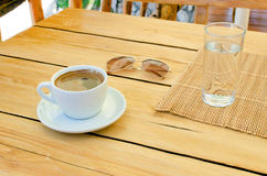 Cup of coffee, glasses, water on table. Relax time with empty space on table Royalty Free Stock Image