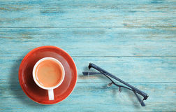 Cup of coffee and glasses on wood table Royalty Free Stock Image