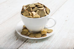Cup of coffee with gold coins Stock Photos