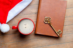 Cup of coffee, golden key, book and santa claus hat on the wonde Royalty Free Stock Image