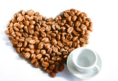A cup and coffee grain as heart Royalty Free Stock Photo