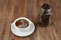 Cup of coffee and grain in a jar Royalty Free Stock Image