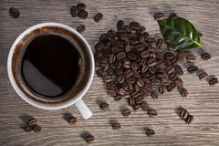 Cup of coffee and grains. A cup of fragrant hot coffee on a wooden table with coffee beans Royalty Free Stock Photos