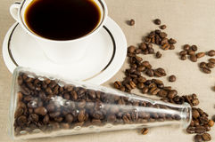 Cup and coffee grains in a glass jar on  linen napkin Royalty Free Stock Photos