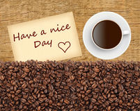 Cup of coffee, grains and Have A Nice Day massage on wooden Royalty Free Stock Photos