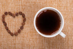 Cup of coffee and grains laid out in a heart shape Stock Photo