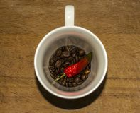 Cup of coffee grains red hot pepper royalty free stock image
