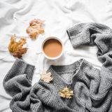 Cup of coffee, gray warm knitted sweater oversize, yellow dry leaves on the bed - cozy home still life royalty free stock photos