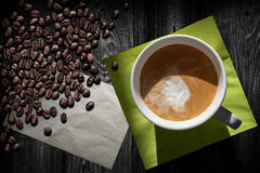Cup of coffee green napkin and beans Royalty Free Stock Photo
