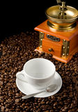 Cup of coffee and grinder on beans Royalty Free Stock Images