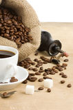 Cup of coffee and grinder with beans Stock Photos
