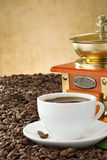Cup of coffee and grinder with beans Stock Images
