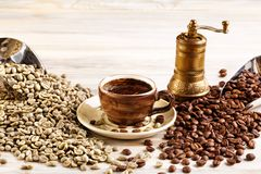 Cup of coffee with the coffee grinder and coffee seeds royalty free stock photo