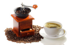 Cup of coffee and grinding mill with coffee seeds royalty free stock photo