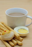 Cup of coffee and grissini, chinese pastry, boiled egg. Sliced in halves on wooden  background Stock Photography
