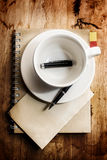 Cup of coffee with grunge notepad and pen on white tablecloth ba Stock Photo