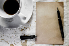 Cup of coffee with grunge notepad and pen Royalty Free Stock Photos