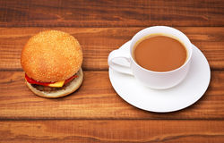 Cup of coffee and Hamburger with fresh tomato, salad, cheese and Stock Photography