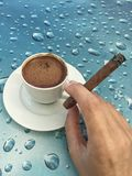 Cup coffee and hand holding a cigar. A cup coffee and hand holding a cigar royalty free stock image