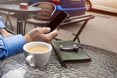 Cup of coffee and hand of man with a cellular telephone for Your advertisement text message royalty free stock images
