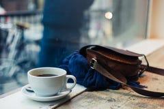 Cup of coffee and handbag by window Stock Photos