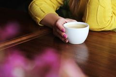 A cup of coffee in the hands of a girl stock photo