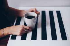 A cup of coffee on wooden texture. A cup of coffee in hands. Morning time Royalty Free Stock Photos