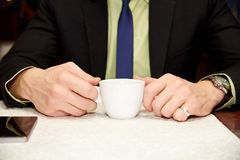 A cup of coffee in hands of a stylish businessman stock photo