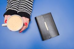 A cup of coffee in the hands of a woman on a blue background. A cup of coffee in the hands of a woman with a book on a blue background stock photography