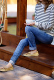 Cup of coffee in hands woman which sits on the wooden steps Stock Photography