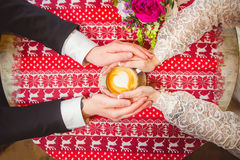 Cup of coffee in hands. Hands of young lovers holding a hot cup of coffee Royalty Free Stock Photo