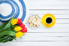 Cup of coffee with hat and tulips Stock Image