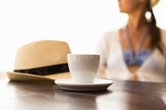 Cup of coffee, hat and woman. At the background Stock Photography