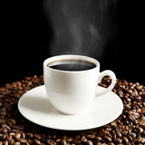 Cup of coffee with haze and coffee beans on black Stock Photo