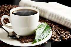 Cup of coffee with haze with newspaper,coffee leaf at breakfast Royalty Free Stock Photography