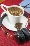 Cup of coffee and headphones Royalty Free Stock Image
