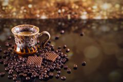 Cup of coffee on heap of roasted coffee beans. Royalty Free Stock Image