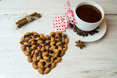 Cup of coffee and heart with almonds on a white background Stock Photography
