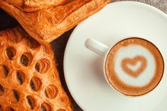 A cup of coffee with a heart and cakes. Royalty Free Stock Photos