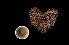 Cup of coffee and the heart of the coffee beans. On a black background Royalty Free Stock Photo