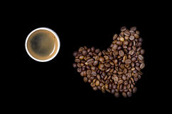 Cup of coffee and the heart of the coffee beans. On a black background Stock Photos