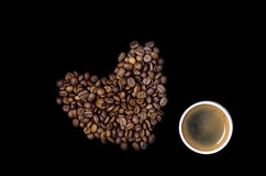 Cup of coffee and the heart of the coffee beans. On a black background Royalty Free Stock Image