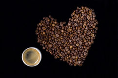 Cup of coffee and the heart of the coffee beans. On a black background Stock Images