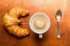 Cup of coffee with a heart of foam, croissants and spoon, top view Stock Photos