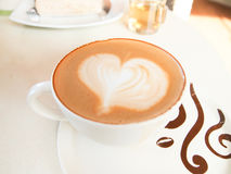Cup of coffee with heart pattern in a white cup Stock Photos