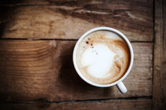 Cup of coffee with heart pattern in a white cup on wooden backgr Royalty Free Stock Image