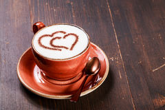 A cup of coffee with heart pattern on wooden background. Latte art Royalty Free Stock Images