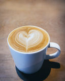 Cup of Coffee with heart pattern on wooden background Royalty Free Stock Photography