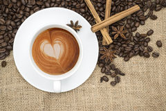 Cup of coffee with heart shape in foam on hessian background Royalty Free Stock Images